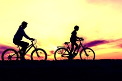 Boy and young girl riding bikes in countryside ,  silhouettes of riding persons at sunset in nature