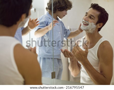 Boy applying shaving foam on his father.