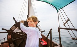 Boy as a captain or sailors play on the ship outdoors on sunny day. Kid driving boat. Captain at the helm controls of a sailing boat in sea.