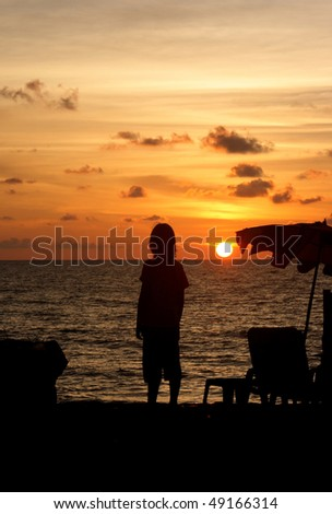 Boy as silhouette in sunset by the ocean