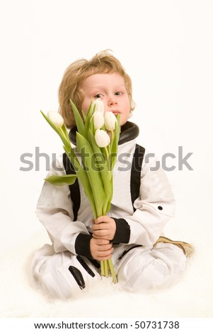 boy astronaut holding a bouquet of white tulips