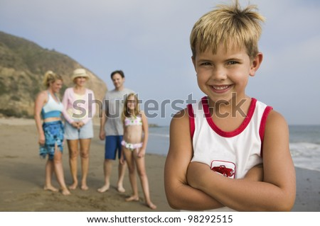 Boy at Beach with His Family in Background