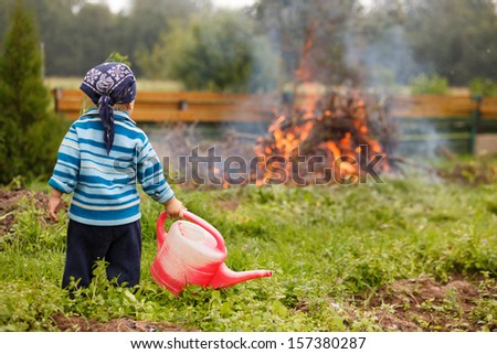 Boy at big fireplace with big watering can helping fight fire