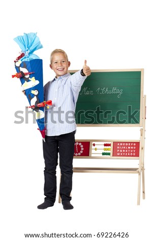 Boy at first school day stands beside chalk board and shows thumb. Isolated on white background.
