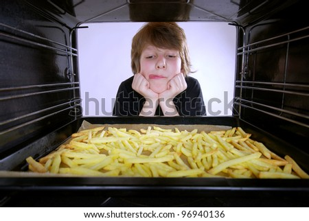 boy at the oven baking french fries