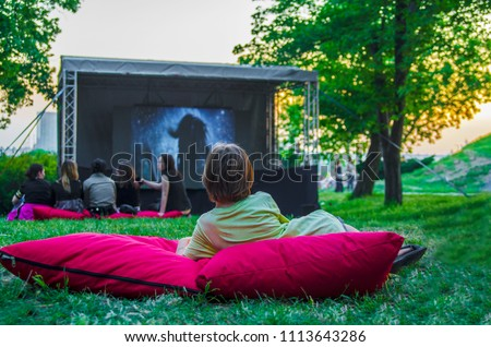 Boy back laying cozy on pillow in green grass and watching film at open cinema in public green park.Perfect spending weekend time in open air.