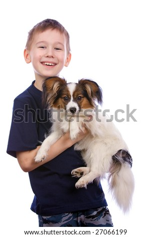Boy bearing a puppy in his arms.