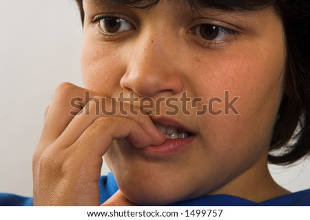 Boy biting his finger nails