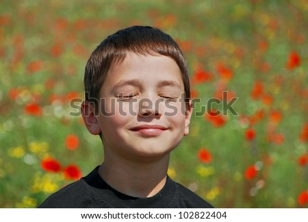 boy blinks from the sun on a blossoming meadow