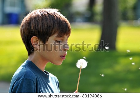 Boy blowing a dandelion outdoors