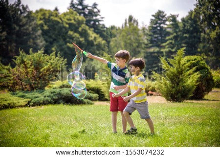 Boy blowing soap bubbles while an excited kid enjoys the bubbles. Happy teenage boy and his brother in a park enjoying making soap bubbles. Happy childhood friendship concept.