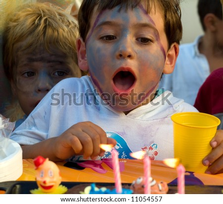 boy blowing the candles of its cake of birthday