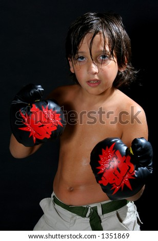 Boy boxing over a black background - stock photo