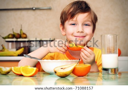boy, breakfast, drinks milk, eats cereal and orange