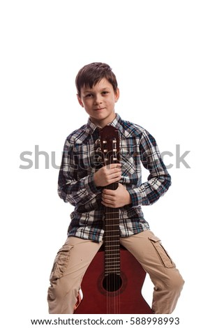 4c0bc5d7eea6a Boy brunette in a plaid shirt with a guitar on a white background in the  studio · Country and western music.