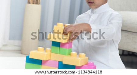 Boy building with colorful toy bricks at home #1134844118