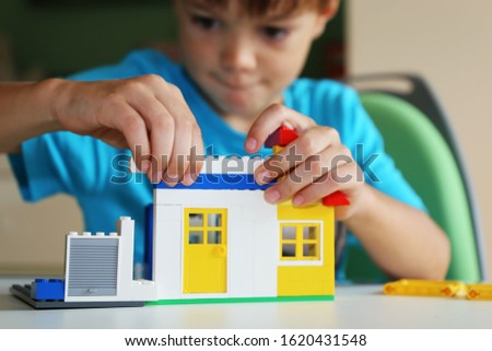 Boy builds a house with building blocks