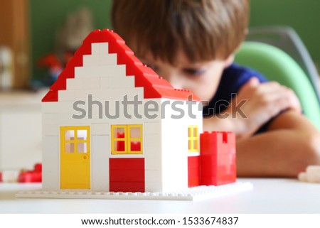 Boy builds a residential with building blocks #1533674837