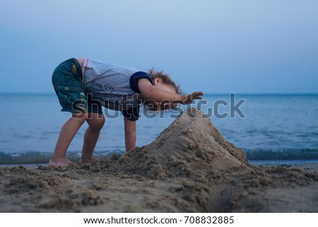 boy builds a sand castle on the beach #708832885