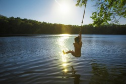 boy bungee jumping over water. kid swings on a rope and ready to jump into the water. Back view. The concept of healthy lifestyle