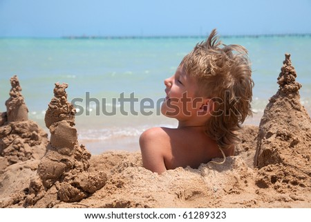 boy buried in sand on the sea beach
