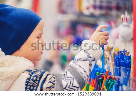 boy buys pens in an office supplies store.