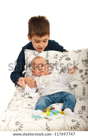 Boy caring his little baby sister  against white background