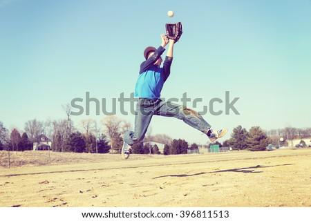 Boy catching a baseball, sandlot baseball, focus on shirt.