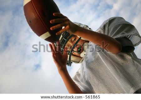 boy catching football, taken from below