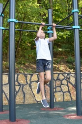 boy caucasian gymnastics outdoor. Little sportsman on the horizontal bar on playground. children's sports for health