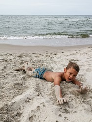Boy child playing at beach sand and water outdoors, copy space