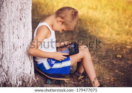 Boy Child playing with Tablet PC Outdoor with Summer nature on background Computer Game Dependence concept Lifestyle