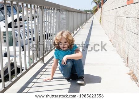 Boy child take short break hunkering down on promenade, rest Stockfoto ©