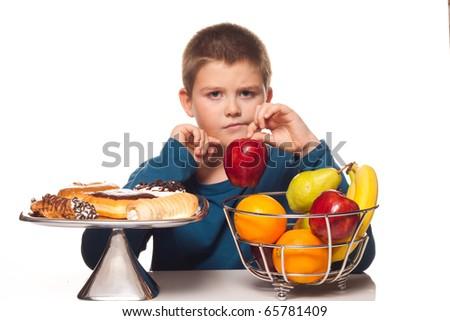boy choosing a healthy apple snack over a dessert