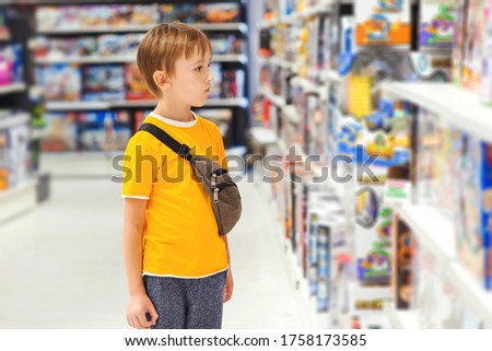 Boy choosing toys in kids store. Many toys around. Kids shop. Sales, discounts and shopping. Cute boy selecting toys in store. Child doing shopping in toys shop.