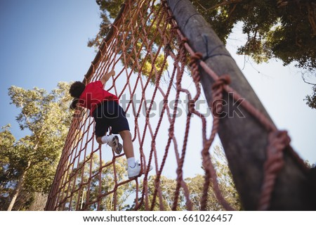 Boy climbing a net during obstacle course in camp