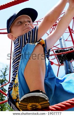 boy climbing on ropes
