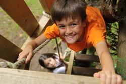 Boy climbing up into a treehouse