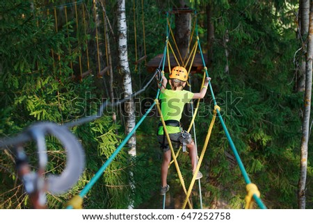 boy climbs in a high wire park above the ground. ziplining. boy on the zip line. kid passes the rope obstacle course. back view #647252758