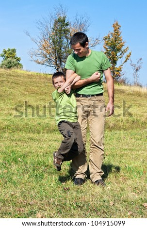 Boy clinging to his father