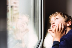 Boy confined at home by the coronavirus crisis in Spain, looks bored out the window without being able to leave home, defocused background.