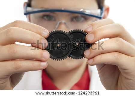 Boy connecting multiple gears while wearing safety glasses, front view.