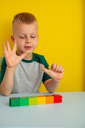 boy counting on his finger.on the table colored figures blocks.On a yellow background