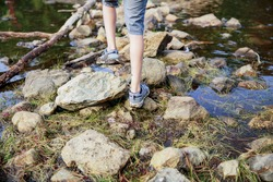 boy crosses the stream. feet boy closeup on a background of forest stream and rocks. The concept of hiking