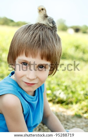 boy cute with chiken on his head nature summer sunny outdoor