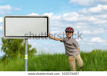 Boy cyclist leaning on blank sign with blue sky and green grass