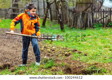 Boy digging on a grass field in the countryside