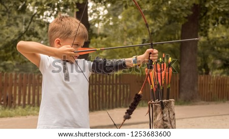 Boy directed arrow at a target. Child with bow and arrow concentrated on target. Kid stared at target. Bowman background. Children and sports. Physical training. Alternative schooling.