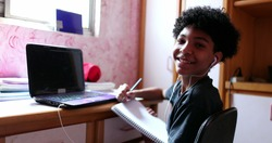 Boy doing homework at home browsing laptop and writing notes. looks at camera smiling