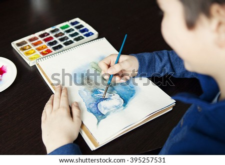 Boy draws a brush and paints to paint a watercolor illustration of a white rabbit in winter #395257531